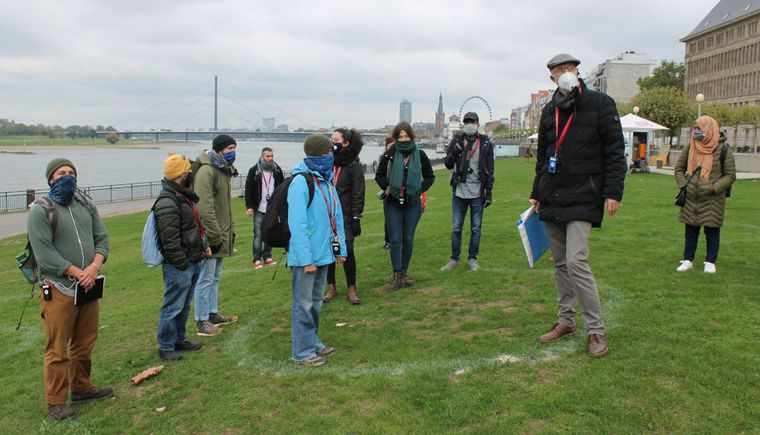 photo group of students with professor, on meadow with river in background