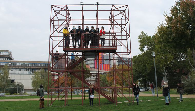 photo group of students with professor on, in front of and beside metal scaffolding
