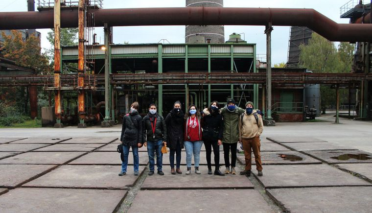 photo group of students with assistant on place with metal plates steel construction in the background
