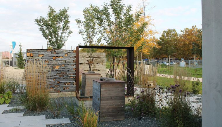 photo garden, pavement with slabs, gravel and grass, art object and wall, background trees